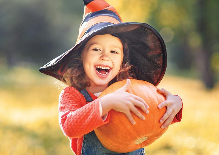 little girl holding pumpkin